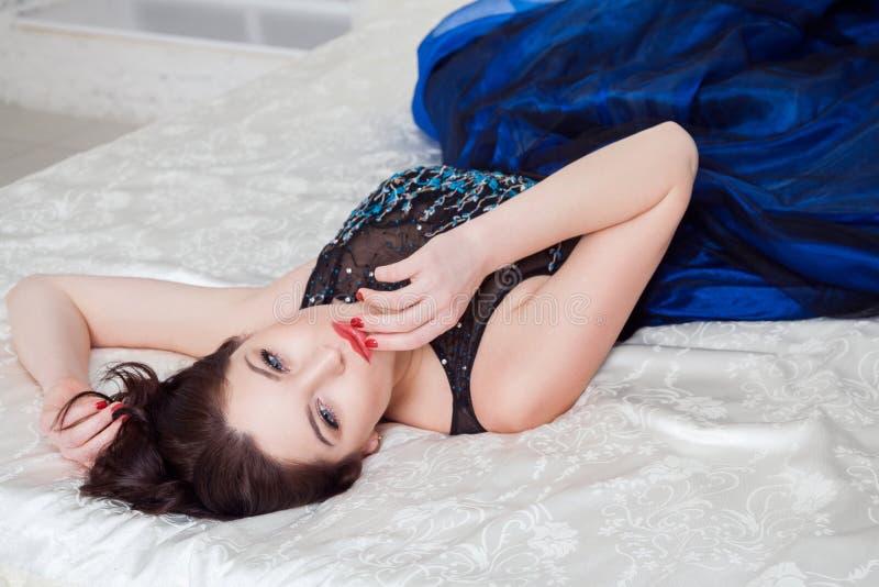 Mujer hermosa en cámara de mirada atractiva del vestido lujoso en con el pasion y el tacto de sus labios rojos mientras que mient fotografía de archivo libre de regalías
