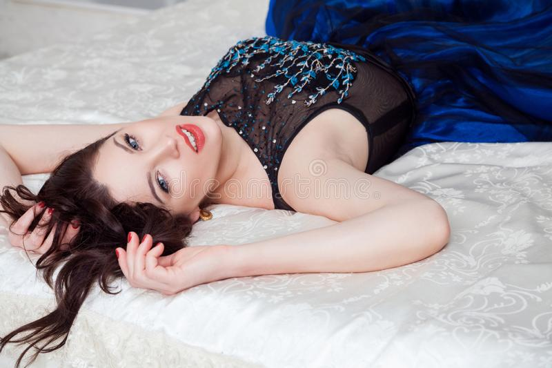 Mujer hermosa en cámara de mirada atractiva del vestido lujoso en, tocando sus pelos y sonrisa dentuda, mientras que miente en la foto de archivo