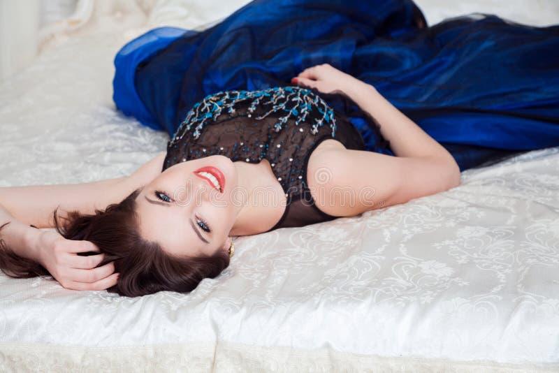 Mujer hermosa en cámara de mirada atractiva del vestido lujoso en y sonrisa dentuda, mientras que miente en la sobrecama blanca d imagenes de archivo