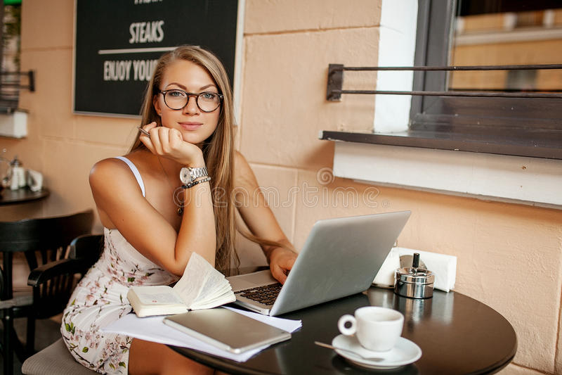 Mujer hermosa en café con el ordenador portátil imagen de archivo
