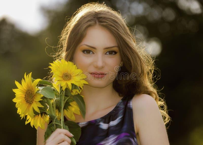 Mujer hermosa en campo floreciente del girasol en verano imagenes de archivo