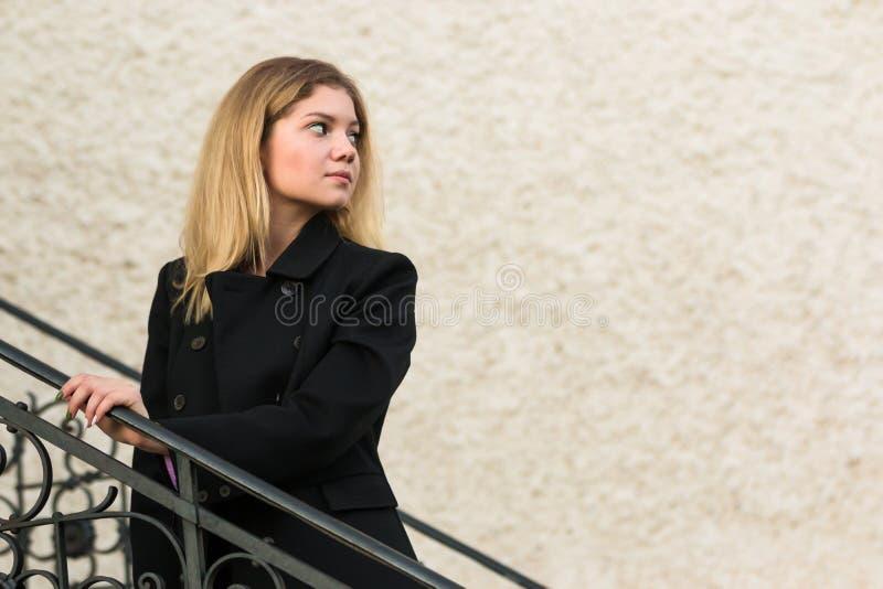 Mujer hermosa en capa negra en las escaleras viejas del castillo en fondo de la pared imagenes de archivo