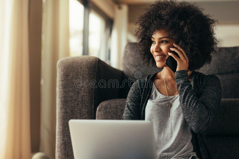 Mujer hermosa en casa con el ordenador portátil y hablar en el teléfono celular fotografía de archivo