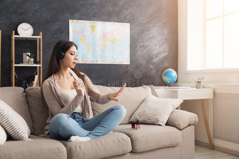 Mujer hermosa en casa que pinta sus clavos mientras que música que escucha imagen de archivo