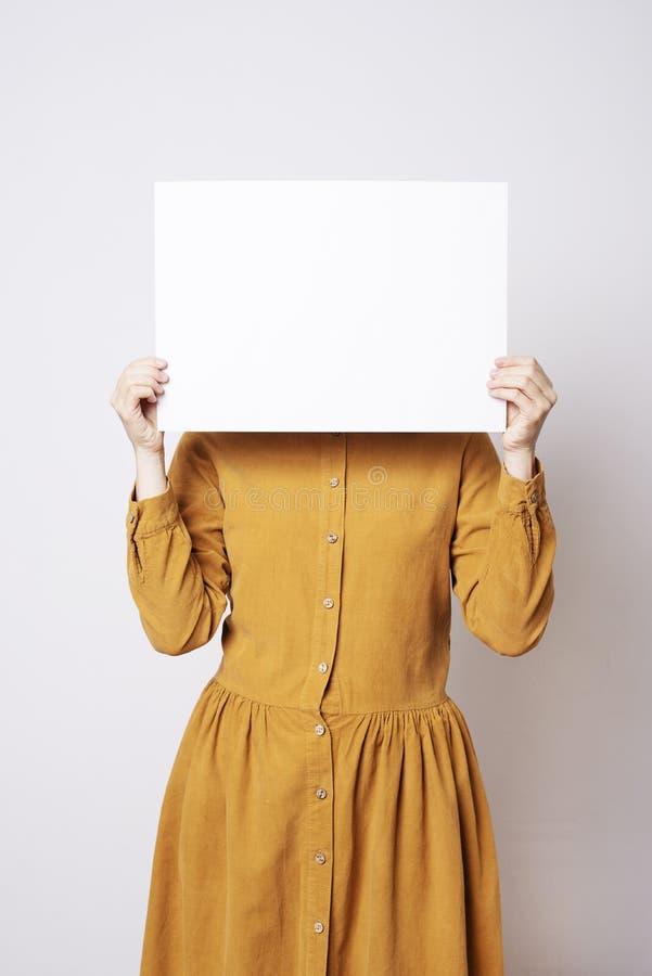 Mujer hermosa en el amarillo que sostiene la tarjeta en blanco foto de archivo libre de regalías