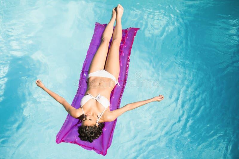 Mujer hermosa en el bikini blanco que se relaja en cama de aire en piscina imagenes de archivo