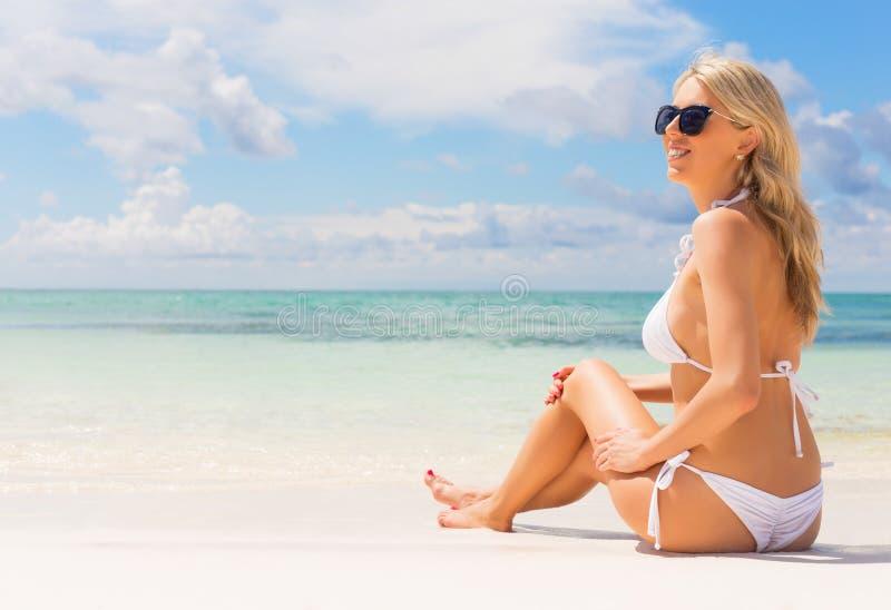 Mujer hermosa en el bikini blanco que se sienta en la playa fotos de archivo libres de regalías