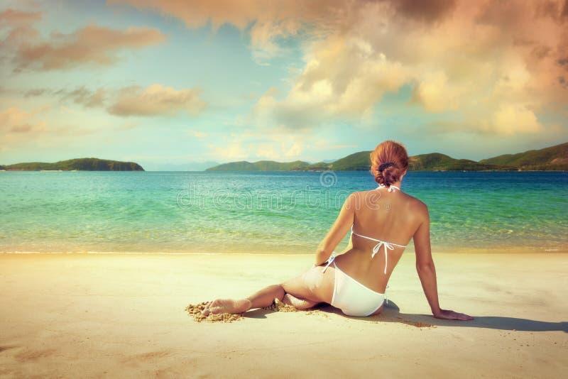 Mujer hermosa en el bikini blanco que toma el sol en la playa en el b fotos de archivo
