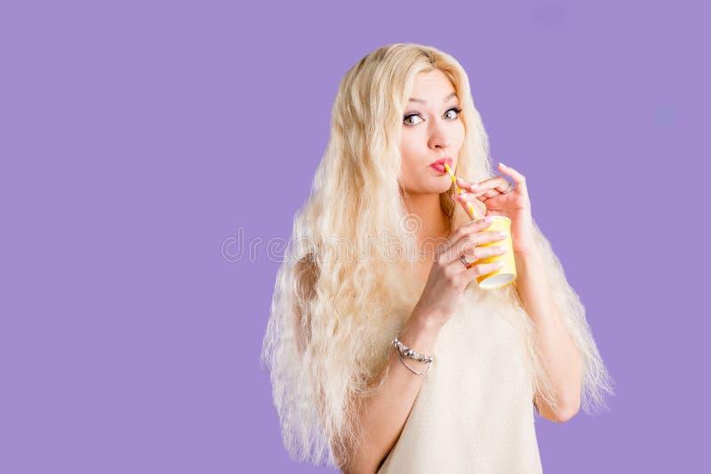 Mujer hermosa en el caf? de consumici?n del fondo violeta del estudio en taza de papel imagenes de archivo