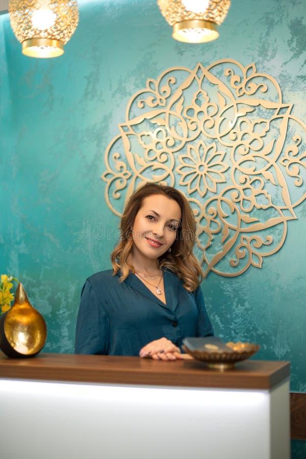 Mujer hermosa en el mostrador de recepción en centro de la yoga y de la salud imágenes de archivo libres de regalías