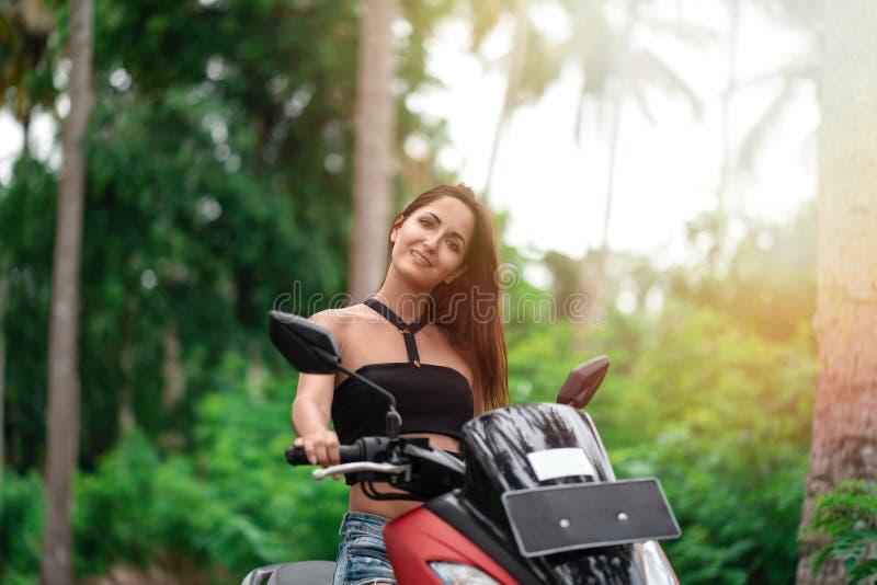 Mujer hermosa en el sol y la conducción de un rojo del ciclomotor en el fondo de palmeras foto de archivo libre de regalías