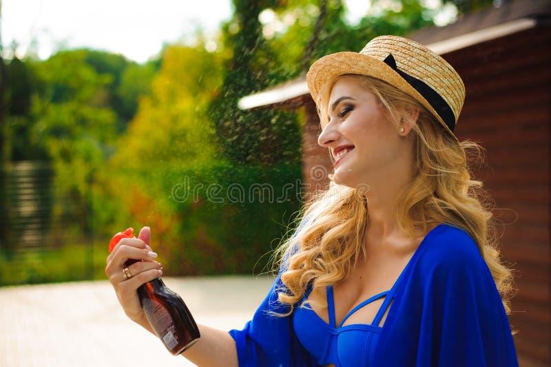 Mujer hermosa en el sombrero que se sienta cerca de una piscina y que aplica el espray de la protección solar en su cuerpo fotografía de archivo