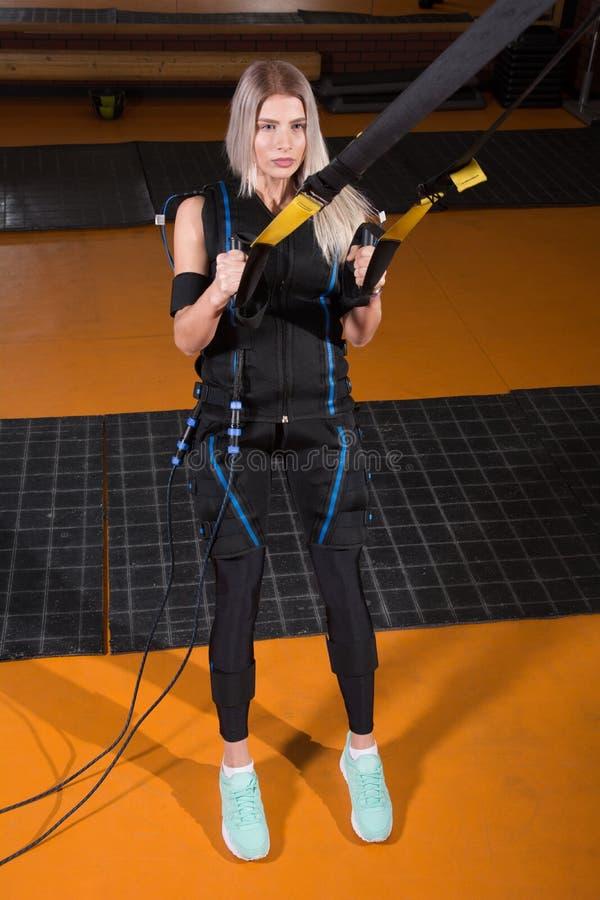 Mujer hermosa en el traje muscular eléctrico del estímulo que hace el ejercicio agazapado para la parte posterior y con la suspen fotos de archivo