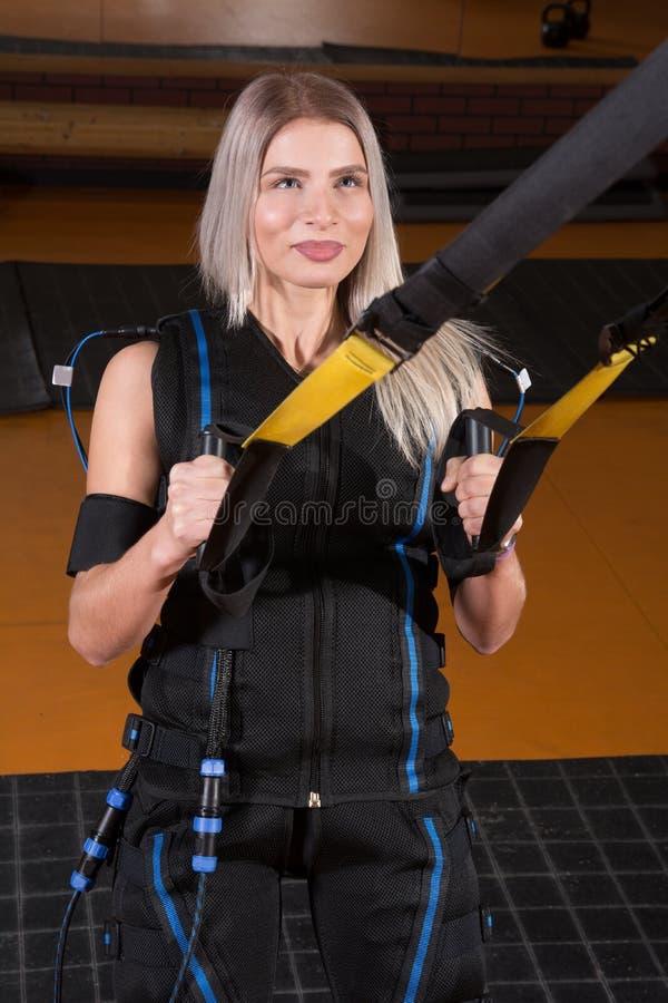 Mujer hermosa en el traje muscular eléctrico del estímulo que hace el ejercicio agazapado para la parte posterior y con la suspen foto de archivo libre de regalías