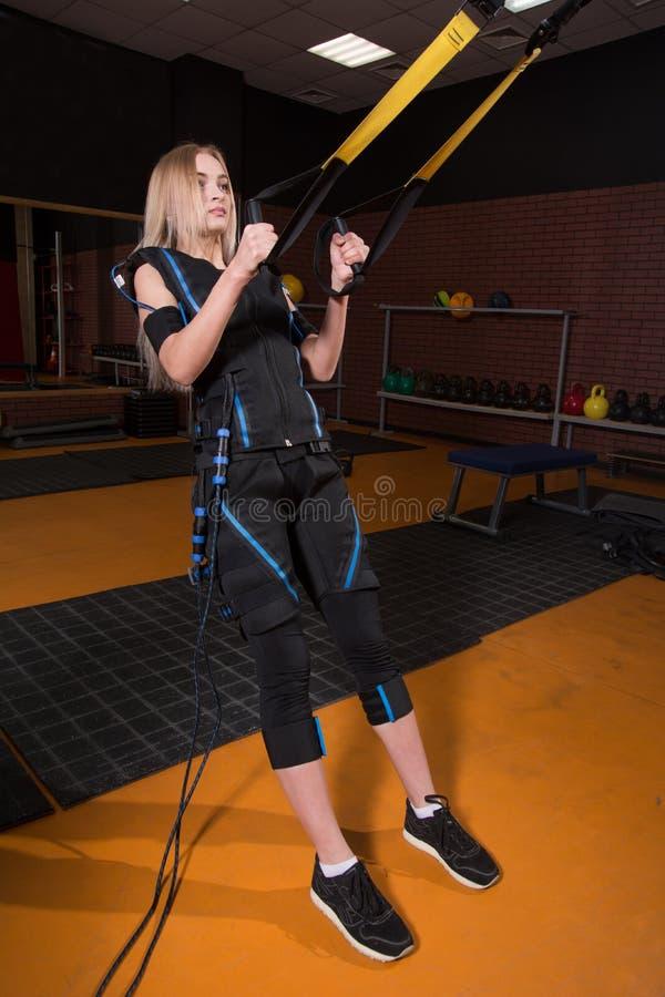Mujer hermosa en el traje muscular eléctrico del estímulo que hace el ejercicio agazapado para la parte posterior y con la suspen foto de archivo