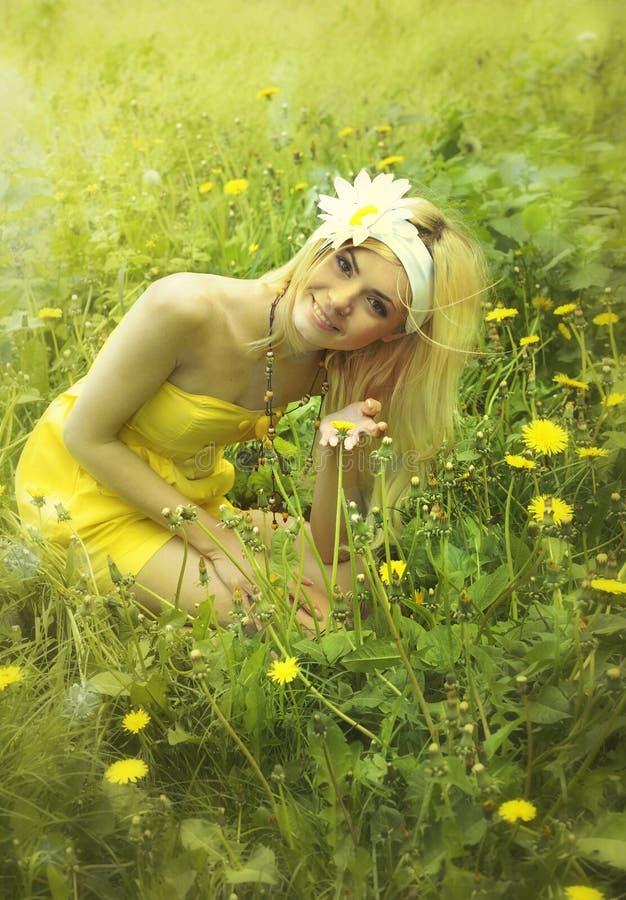 Mujer hermosa en el vestido amarillo que se sienta en una hierba. imagen de archivo libre de regalías
