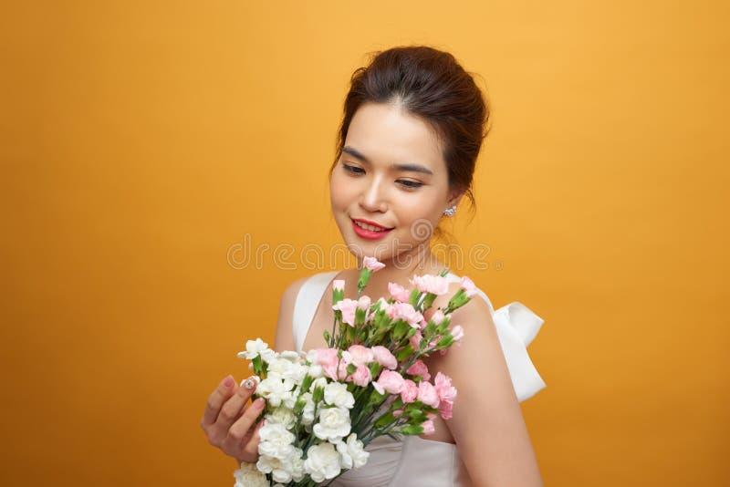 Mujer hermosa en el vestido blanco con el clavel de las flores en manos en un fondo amarillo Ella tiene sonrisa apacible foto de archivo libre de regalías