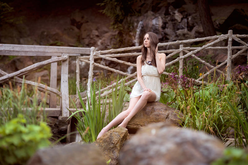 Mujer hermosa en el vestido blanco que se sienta en la naturaleza foto de archivo libre de regalías