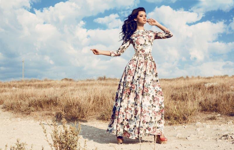 Mujer hermosa en el vestido de flores lujoso que presenta en campo del verano imagen de archivo libre de regalías