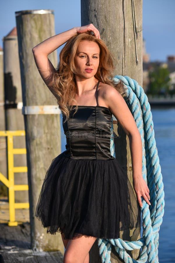 Mujer hermosa en el vestido negro elegante que presenta en el embarcadero que mira in camera imagen de archivo