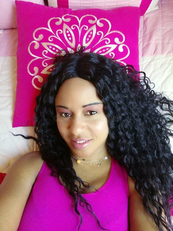 Mujer hermosa en fotografía del lecho con el pelo negro rizado foto de archivo