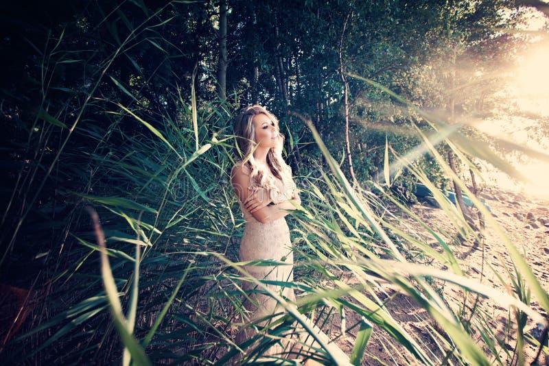Mujer hermosa en hierba verde y Sunligth fotografía de archivo libre de regalías