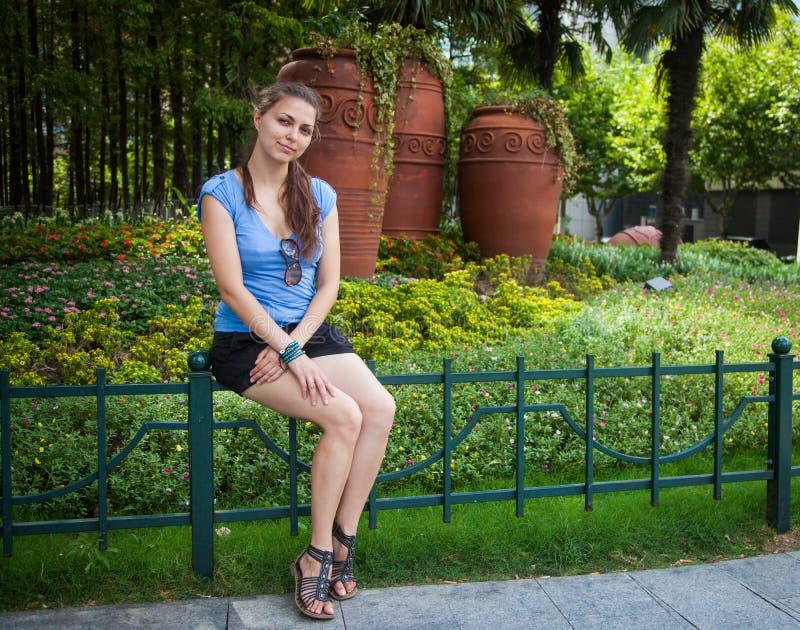 Mujer hermosa en la camiseta azul, pantalones cortos negros y sandalias del calzado sentándose en la verja del metal en el parque fotografía de archivo libre de regalías
