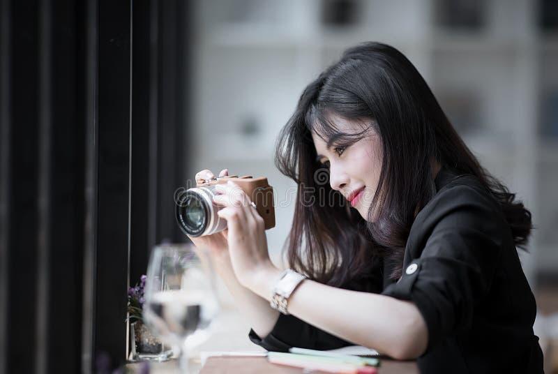 Mujer hermosa en la habitación negra que sostiene la cámara, mirando la pantalla fotos de archivo