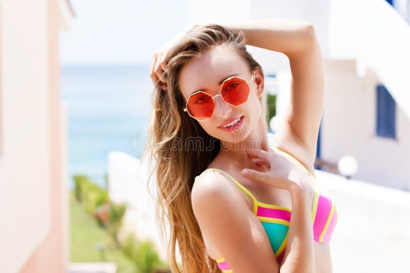 Mujer hermosa en la presentación roja de las gafas de sol al aire libre en verano en la isla tropical en tiempo caliente en la fo imagen de archivo