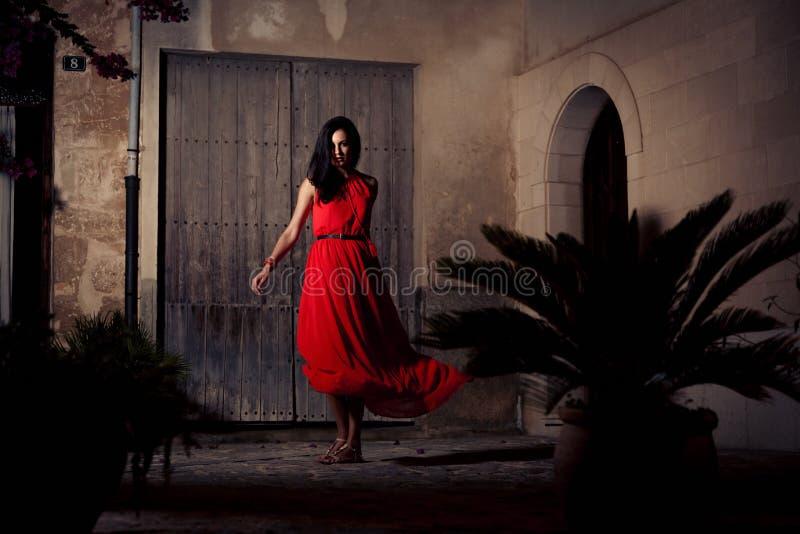 Mujer hermosa en la presentación roja del vestido imágenes de archivo libres de regalías