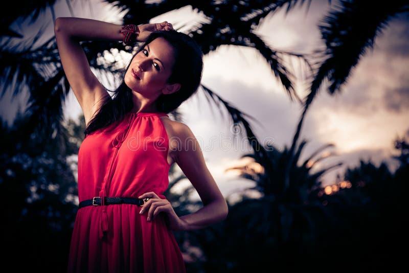 Mujer hermosa en la presentación roja del vestido fotografía de archivo