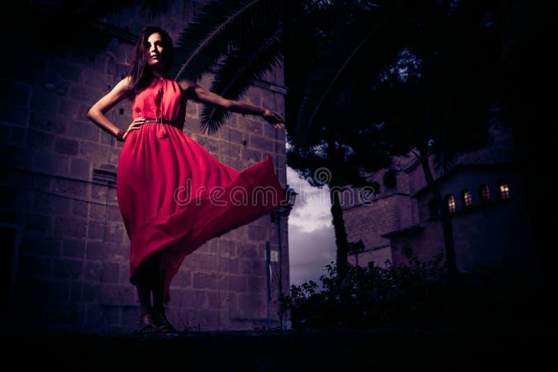 Mujer hermosa en la presentación roja del vestido foto de archivo libre de regalías