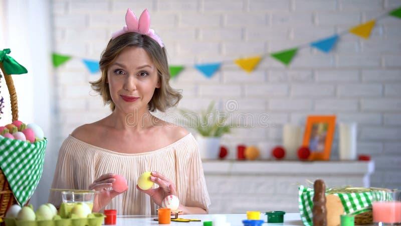 Mujer hermosa en la venda linda que sostiene los huevos teñidos, tutorial para los artes de Pascua imágenes de archivo libres de regalías