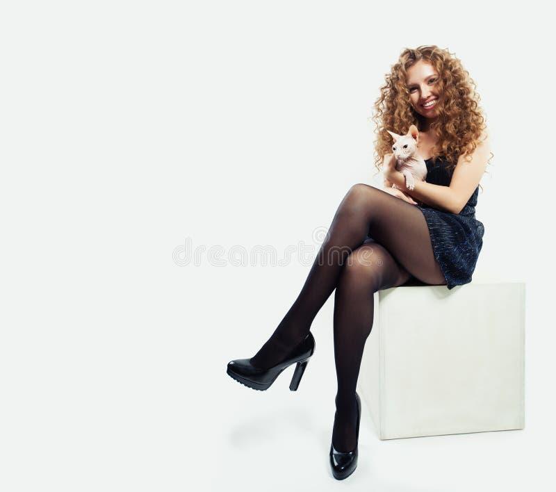 Mujer hermosa en medias negras y zapatos de los tacones altos que sostienen el gato sin pelo en el fondo blanco imagen de archivo libre de regalías