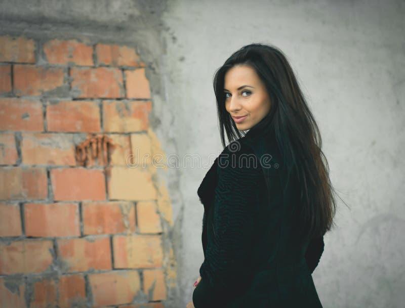 Mujer hermosa en negro cerca del brickwall Tiro de la manera imágenes de archivo libres de regalías