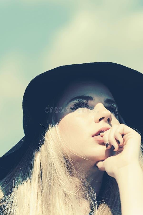 Mujer hermosa en sombrero Manera retra sombrero del verano con el borde grande sobre fondo del cielo azul fotografía de archivo libre de regalías