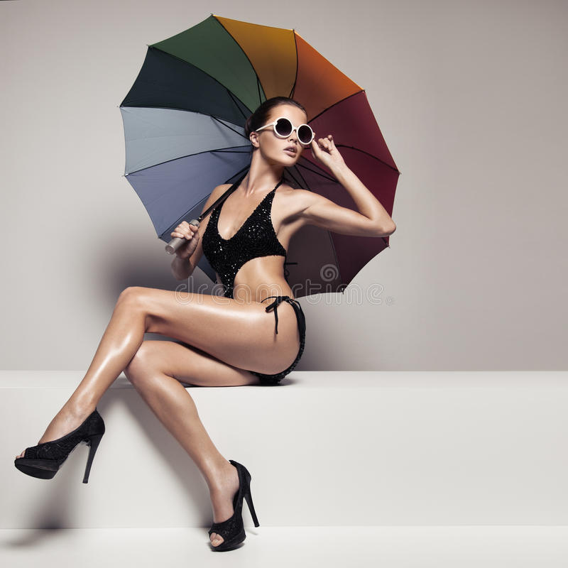 Mujer hermosa en traje de baño y gafas de sol que sostienen el paraguas fotos de archivo libres de regalías