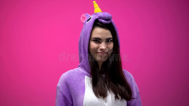 Mujer hermosa en traje divertido del unicornio que sonr?e y que presenta para la c?mara, diversi?n foto de archivo