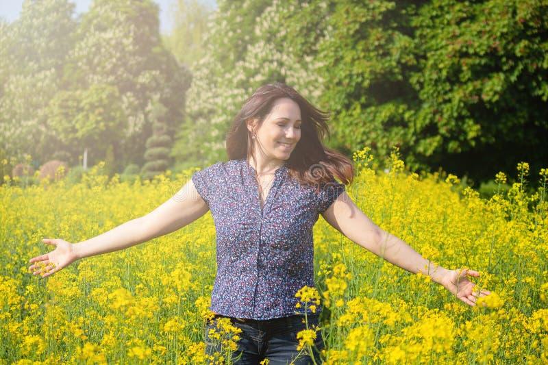 Mujer hermosa en un campo de flores amarillo imagenes de archivo