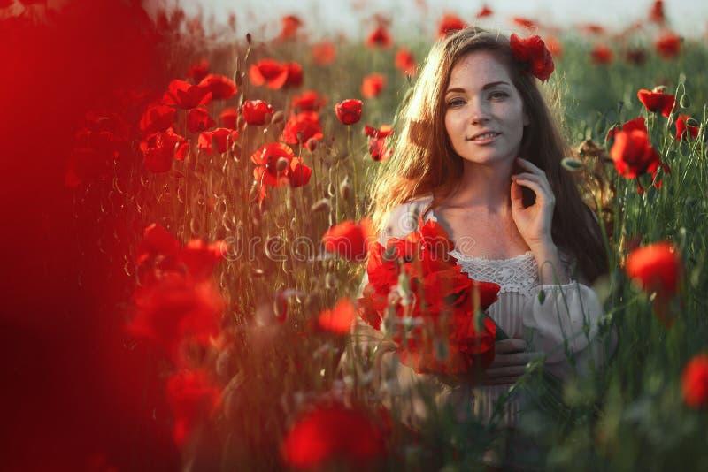 Mujer hermosa en un campo de la amapola fotos de archivo