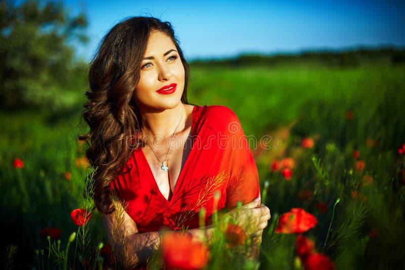 Mujer hermosa en un campo de la amapola con las flores imagen de archivo libre de regalías