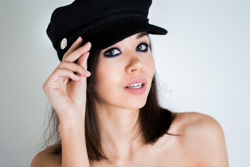 Mujer hermosa en un casquillo negro, con el maquillaje profesional mirando la cámara en el fondo blanco fotos de archivo