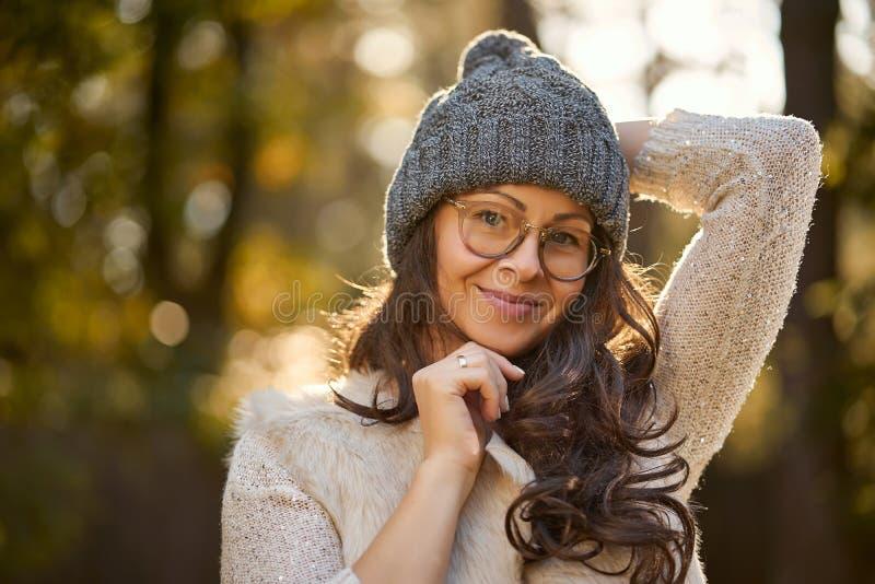 Mujer hermosa en un casquillo y vidrios en un fondo del bosque del otoño foto de archivo