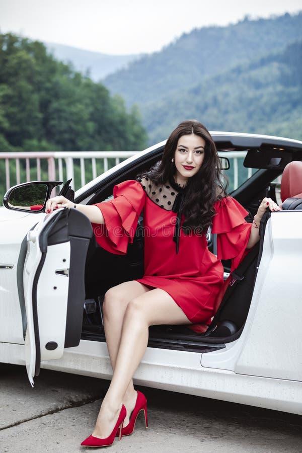 Mujer hermosa en un coche convertible que disfruta de un día de verano imagenes de archivo