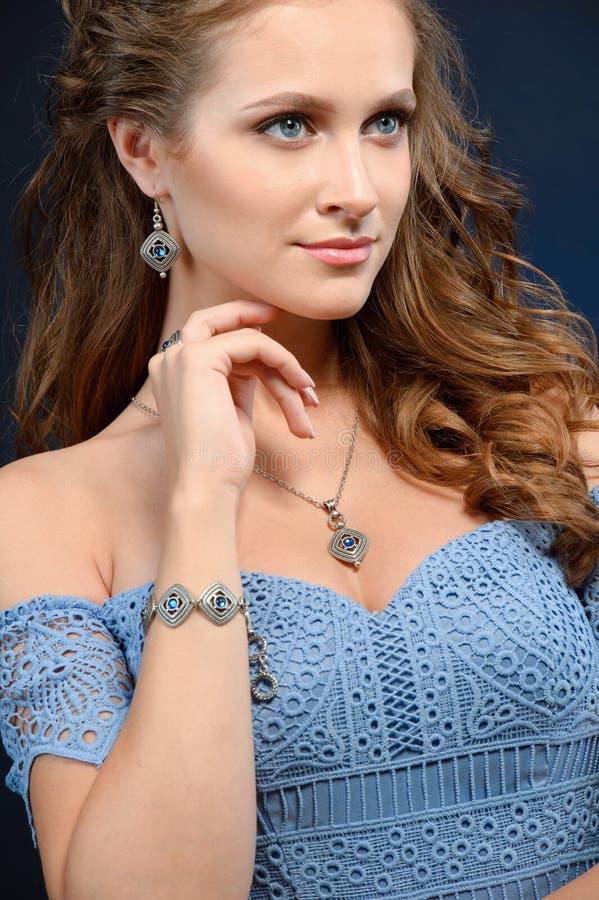Mujer hermosa en un collar, pendientes y anillo Modelo en joya fotos de archivo