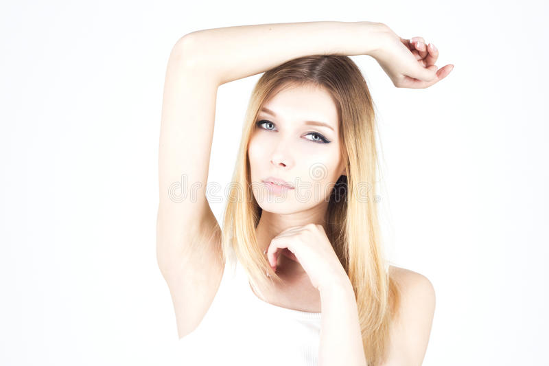 Mujer hermosa en un fondo blanco con su mano aumentada Encerar el axila foto de archivo