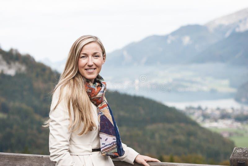 Mujer hermosa en un impermeable y una bufanda imágenes de archivo libres de regalías