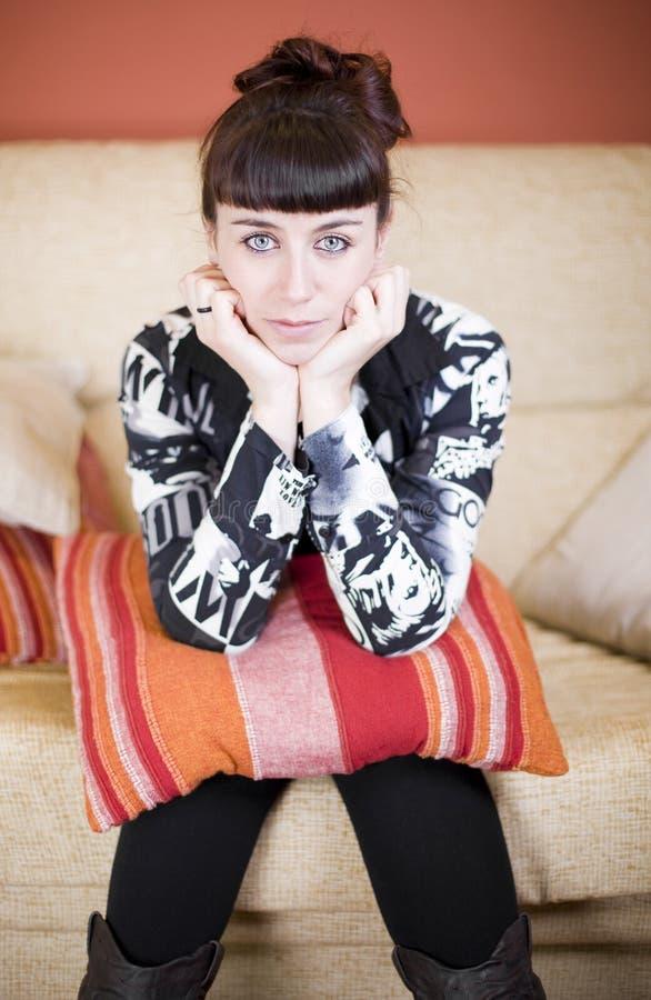 Mujer hermosa en un sofá foto de archivo