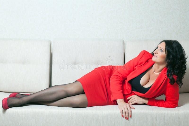 Mujer hermosa en un sofá blanco imágenes de archivo libres de regalías