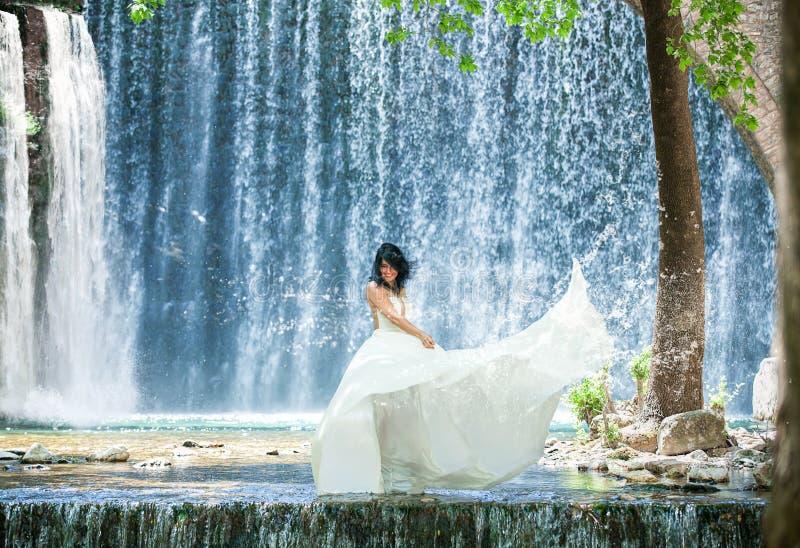 Mujer hermosa en un traje blanco que se coloca en el agua delante de una cascada grande fotografía de archivo libre de regalías